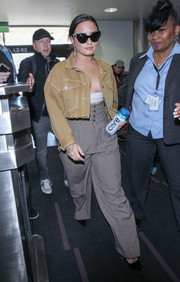Demi Lovato caught a flight out of LAX wearing a cropped denim jacket by Urban Outfitters.