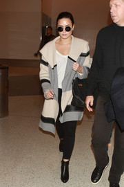Demi Lovato took a flight keeping warm in a color-block wool and cashmere coat by Vince.