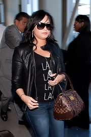 Demi Lovato carried a brown checkered canvas tote with leather trim through LAX.
