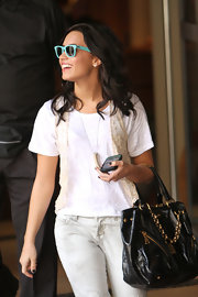 Demi adds instant edge to her all white look with this chain strap zipper tote.