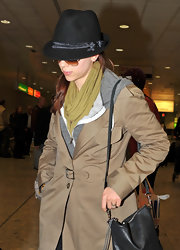Most celeb's try and conceal their identity when they're in airports just like Scarlett is attempting to do here. She wore a black fedora with a cool tan trench coat.