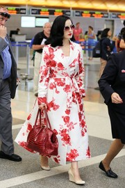 Dita Von Teese cut an ultra-feminine figure at LAX in her red and white floral trenchcoat.