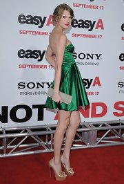 Taylor Swift arrived at the premiere of 'Easy A' at Grauman's Chinese Theatre wearing a gold sequin clutch, which she paired with a green satin dress and platform pumps.