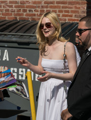 Elle Fanning headed to 'Kimmel' wearing chic brown cateye shades.