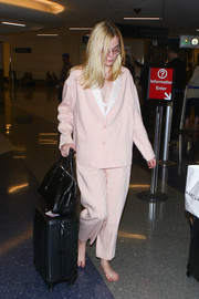 Elle Fanning made her way through LAX wearing a baggy pink pantsuit and no shoes!
