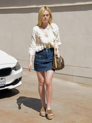 Elle Fanning chose a denim mini skirt to team with her frilly top.