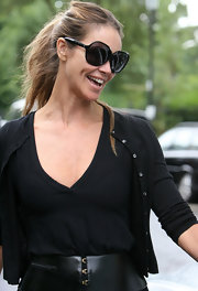 Elle wore a simple ponytail with dark, oversized shades.