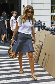 Elle looked summer-chic in a knee-length denim skirt with a loose, white tee and metallic sandals.