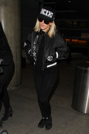 Ellie Goulding kept it comfy in a black varsity jacket and a pair of leggings during a flight to LAX.