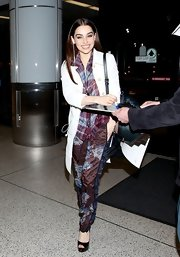 Emilia Clarke mixed prints and textures while traveling when she wore these silk, floral print pants.