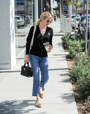 Emma Roberts stayed cozy in a black V-neck cardigan by Coach while out and about.