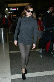 Emma Watson kept cozy with a gray Joseph turtleneck sweater for a flight.