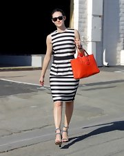 Emmy Rossum injected some color into her monochrome outfit with a bright red leather tote.