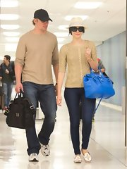 Emmy Rossum added a shock of color to her neutral traveling get-up with a bright blue cross-body tote.
