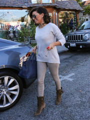 Eva Longoria completed her monochromatic ensemble with tan suede boots by Chloe.