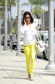 Eva stepped out looking casual but chic in this white V-neck sweater and neon yellow pants.