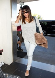 Eva Longoria kept it relaxed yet chic in a white scoopneck sweater by Helmut Lang while catching a flight at LAX.