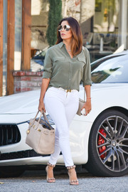 Eva Longoria paired an olive-green silk button-down by Equipment with skintight white jeans for a casual-chic look.