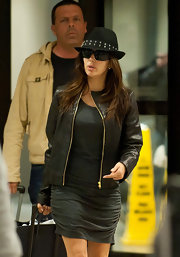Eva Longoria finished off her edgy airport look with a studded fedora.