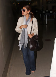 Eva Mendes made her way out of the infamous LAX airport looking comfy cozy in her wide legged pants and grey scarf. She accessorized with a pair of round sunglasses and a brown leather shoulder bag.
