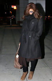 Eva Mendes arrived at JFK airport in New York and hid her face in a warm, black wool scarf that was tucked into her coat.