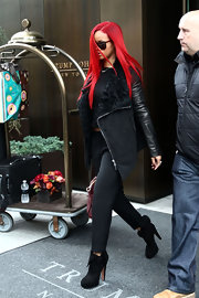 Rihanna struts in cool suede ankle boots befitting of the uber trendy singer. Flaps on the boots are a chic touch to the look.