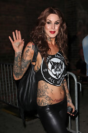 Kat Von D wears a skimpy top to show off her rose tattoo, on her right side.