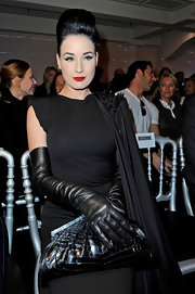 Dita Von Teese is perfectly accessorized, right down to her black alligator frame clutch.