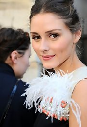 Olivia Palermo wore barely-there makeup to the Giambattista Valli show in Paris. To try her neutral eye look, sweep a soft taupe shadow across upper lids and blend lightly up into crease. For more definition work a small amount of chocolate brown eyeshadow into the upper lash and apply a coat of mascara.