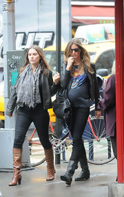 Gisele braved the rain with a gal pal in skinny jeans topped off with flat black leather boots complete with buckled detailing.
