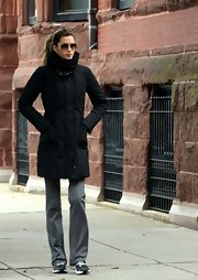 Gisele Bundchen bundled up in a long black puff coat and slouchy pants.