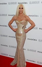 Donatella Versace showed off her impossibly tiny figure in this champagne corset gown.