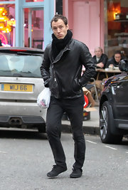 Jude stays warm in all black wearing an leather jacket with an asymmetrical zip.