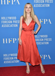 Dakota Fanning was classic and feminine in a red silk wrap dress by Nina Ricci at the HFPA Grants Banquet.