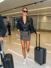 Hailey Clauson teamed white basketball sneakers with a black leather jacket and a gray mini dress for a flight.