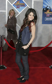 Selena styles up her ensemble with a denim vest over her romper and jeans.