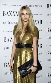 Cara Delevingne belted her glittery dress to show her waist at the Harper Bazaar's Women of the Year Awards.