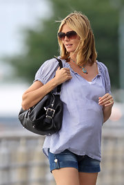 While strolling in NYC Heidi carries every girls essential black leather shoulder bag.