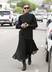 Irina Shayk completed her goth look with a black midi skirt and combat boots.