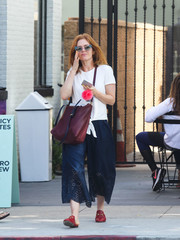 Isla Fisher completed her ensemble with a maroon leather shoulder bag.