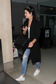 Jaimie Alexander completed her grunge-chic airport look with a pair of ripped jeans.