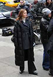 Saffron Burrows cozied up in a long black down coat while filming 'Law and Order.'