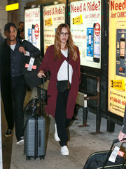 Jessica Alba arrived on a flight at JFK wearing a wine-colored duster by Babaton.