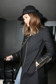 Jessica Alba paired a black Maison Michel fedora with a military coat for a chic airport look.