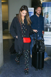 Jessica Alba accessorized her pajama-inspired set with a pop of color when she wore a red crossbody purse at LAX.