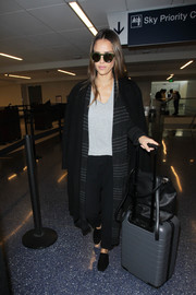 Jessica Alba kept cozy in a black wool coat layered over a long striped cardigan while catching a flight.