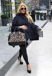 Jessica Simpson tried to hide her baby bump in a navy blue caplet paired with black platform pumps.