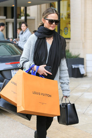 Chrissy Teigen paired a fringed black scarf with a gray sweater for her shopping outfit.