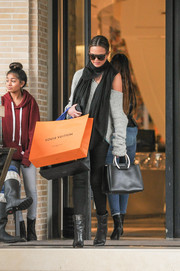 Chrissy Teigen had her hands full with a chic black leather tote and some shopping bags.