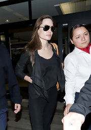Angelina donned a black crop jacket with her dark ensemble and aviators at LAX.